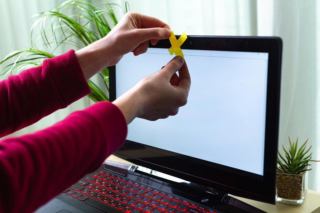 persona protegiendo la webcam de su laptop