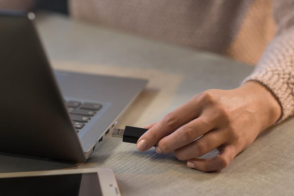 persona ingresando USB a laptop