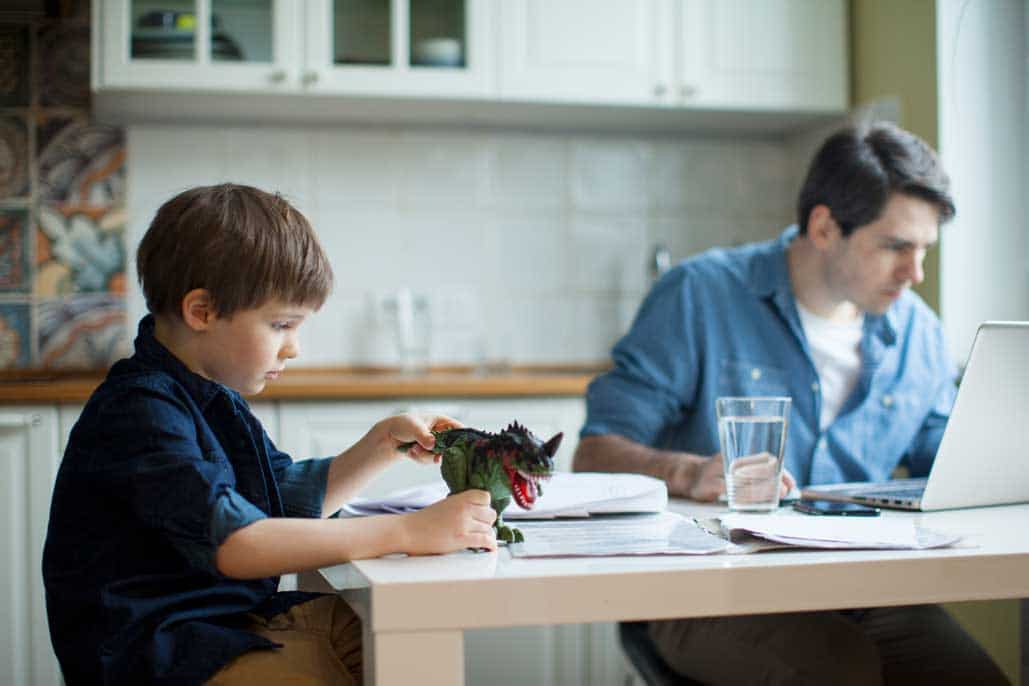 dad working from home and kid playing besides him