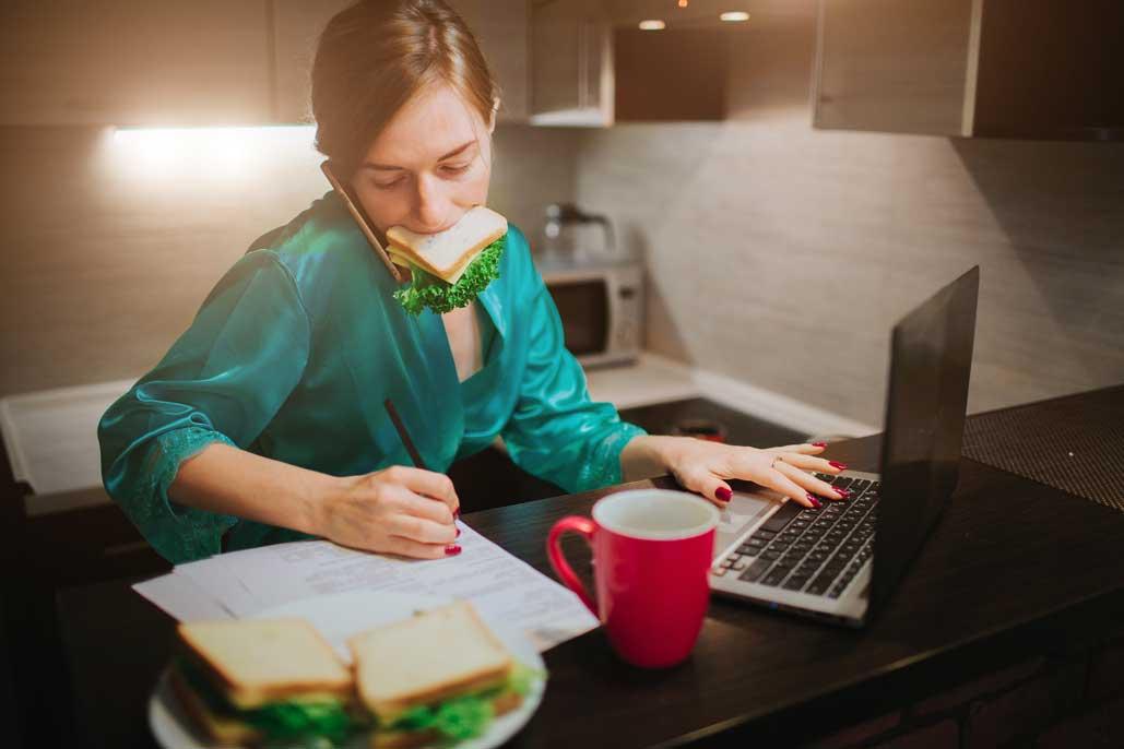 mujer comiendo mientras trabaja desde casa